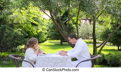 Couple in the white bathrobes have breakfast in the garden
