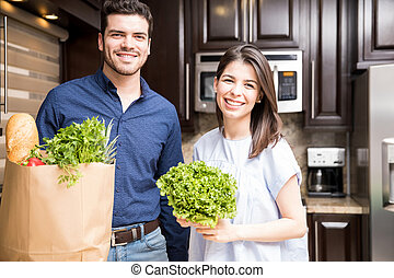 Couple in their kitchen with a shopping bag of groceries