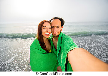 Couple in towels on the beach
