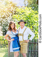 Couple in traditional bavarian clothes standing in the garden