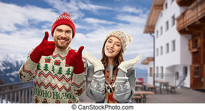 couple in ugly christmas sweaters over ski resort