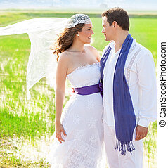Couple in wedding day with wind on veil