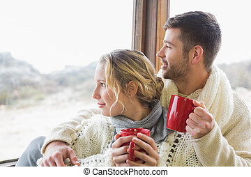 Couple in winter wear with cups looking out through window -...