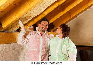 Couple installing thermal insulation to roof