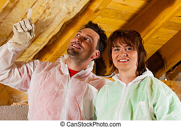 Couple installing thermal insulation to roof - Couple...