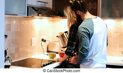 Couple interacting while having coffee in kitchen 4k -...