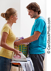 Couple ironing clothes