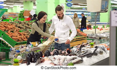 Couple is choosing fish and smiling while doing shopping at the supermarket.
