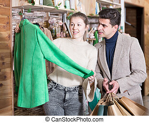 Couple is choosing jacket for her