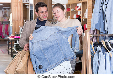 Couple is choosing jeans blouse for her
