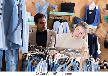 Couple is choosing jeans clothes for her