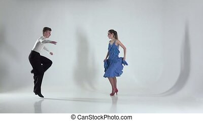 Couple is dancing rumba on white background, shadow. Slow motion