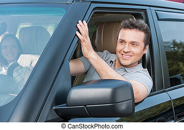 Couple is driving in a car, man is looking out of window and...