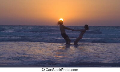 Couple is falling in love on beach at sunset. Young woman with husband is holding hands and circling on shore of the sea. Sexy girl and guy with long hair, have fun under the sun. Romantic evening