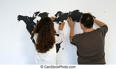Couple is fixing the world map on the wall