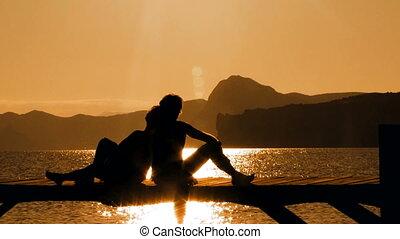 Couple is meeting sunset on a bridge