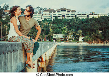 Couple is relaxing on the pierce watching the sea.