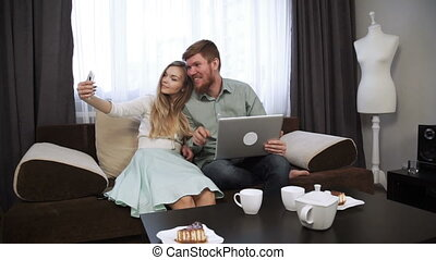 Couple is sitting on the couch sofa at home Do selfie photo on smartphone Look at the laptop screen and smile
