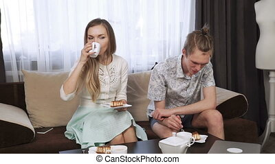 Couple is sitting on the couch sofa at home, Drink tea from a white tea set.