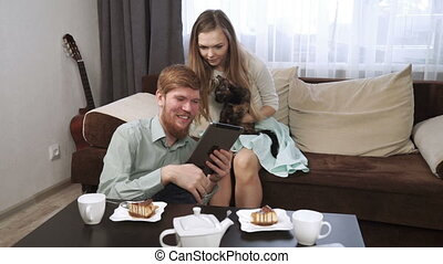 Couple is sitting on the couch sofa at home Look into the tablet and smile, Drink tea from a white tea set and watching tv.