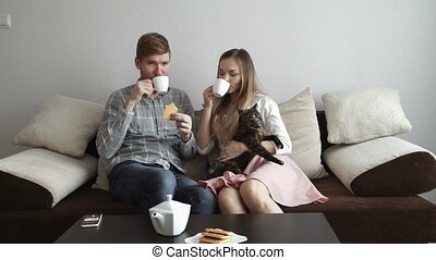 Couple is sitting on the couch sofa at home stroking a cat, Drink tea from a white tea set and watching tv.