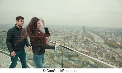 couple is standing on roof of high building of skyscraper in...