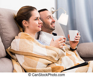 Couple is watching TV on the sofa