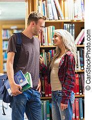 couple, jeune, bibliothèque, contre, étagère, sourire