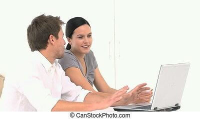 couple, jeune regarder, leur, quelque chose, ordinateur portable