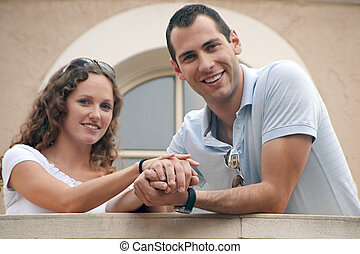 couple, jeune, séduisant, tenant mains, sourire, balcon