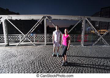 couple jogging across the bridge in the city