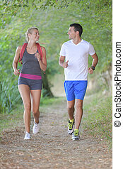 couple jogging in the woods