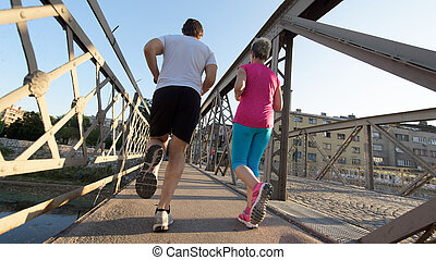 couple jogging - healthy mature couple jogging in the city...