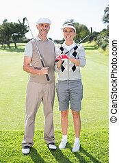 couple, jouer golf, tenue, sourire, appareil photo, clubs