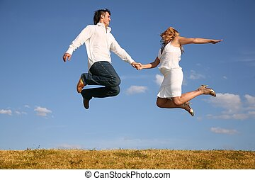 couple jump on meadow