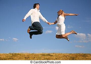 couple jump on meadow