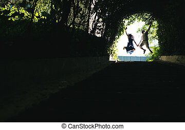 couple jumping in the end of tunnel with trees
