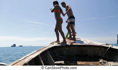 Couple Jumping In Water From Long Tail Boat Nose, Young Man...