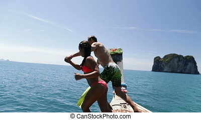 Couple Jumping In Water Holding Hands From Long Tail Boat...