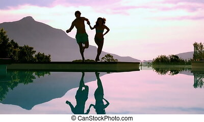 Couple jumping into swimming pool holding hands in slow...