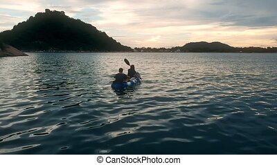 Couple in kayak in waters of Monkey Bay Lake Malawi. Drone shot.