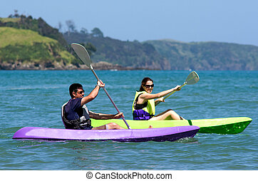 Couple kayaking at sea - Attractive couple kayaking at sea.