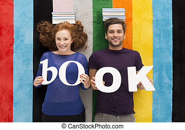 Couple keeping a pile of books on their head