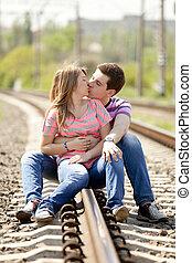 Couple kissing at railway.