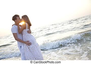 Couple kissing at sunrise