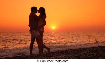 Couple kissing at sunset by the sea