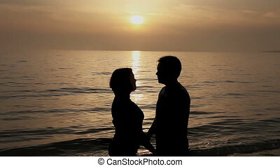 Couple kissing at sunset on beach