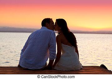 couple kissing at sunset sitting in jetty at orange sea lake