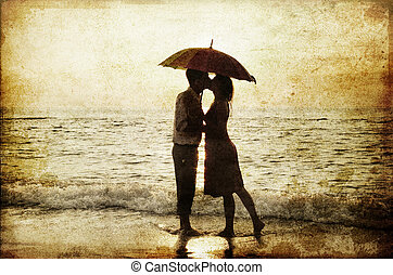 Couple kissing under umbrella at the beach in sunset. Photo in old image style.