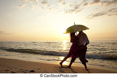 Couple kissing at the beach in sunset.